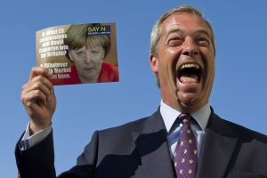"""Leader of the UK Independence Party (UKIP) Nigel Farage, poses with a leaflet showing a picture of German Chancellor Angela Merkel in Cliftonville, Margate, east of London, as he kicks off their """"Say No To The EU"""" tour on September 7, 2015, during the partys referendum campaign. AFP PHOTO / JUSTIN TALLIS        (Photo credit should read JUSTIN TALLIS/AFP/Getty Images)"""